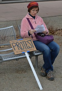"Woman sitting next to her ""multi-use protest sign"" at ""Resist Trump Tuesdays"" rally in Denver."