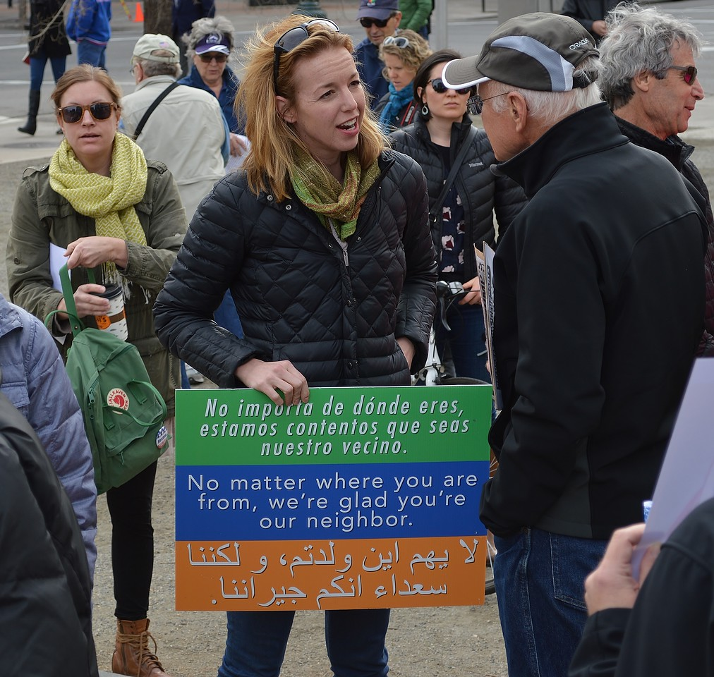 Woman holds sign in Spanish, English, and Arabic, about neighbors.