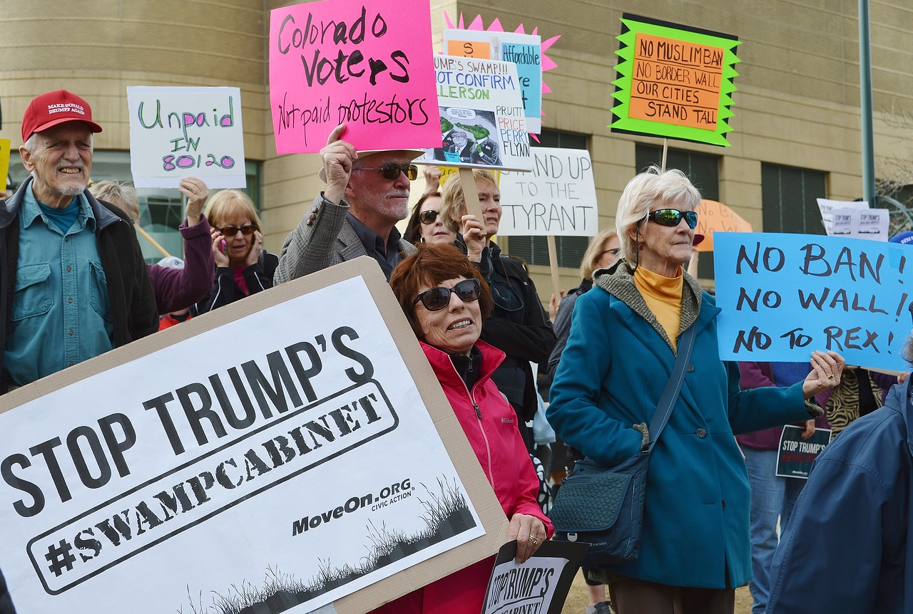 "Protesters with signs at ""Resist Trump Tuesdays"" rally in Denver."