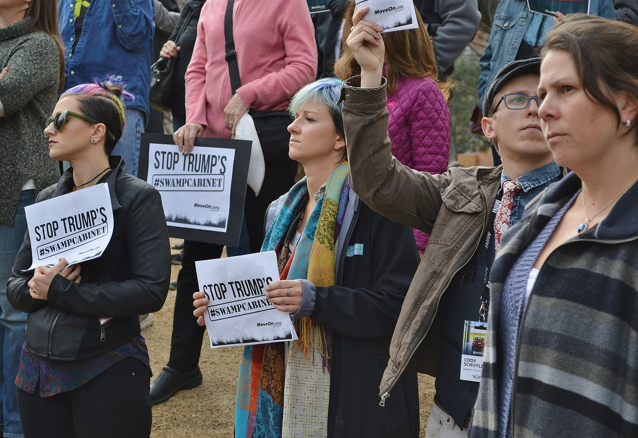 """Protesters with signs at """"Resist Trump Tuesdays"""" rally in Denver."""