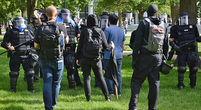 """Police face off with counter demonstrators as they try to clear a park after a """"Stop Sharia Law"""" rally in Denver."""
