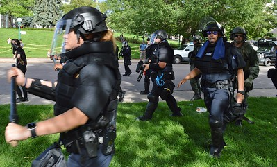 """Police clear a park of counter demonstrators after a """"Stop Sharia Law"""" rally in Denver."""
