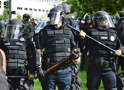 """Police in riot gear keep counter demonstrators separate from the """"Stop Sharia Law"""" rally in Denver."""
