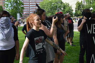 """Young woman gestures and yells at police facing off with counter demonstrators after a """"Stop Sharia Law"""" rally in Denver."""