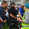 A supporter and an opponent of President Trump have a friendly exchange at a rally in Denver as  a police officer looks on.