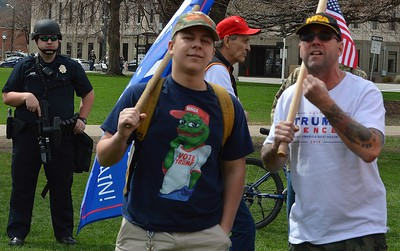Trump supporter gestures at anti-Trump protesters as they exchange words at a pro-Trump rally in Denver.
