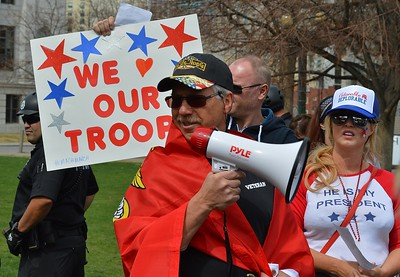 This supporter of President Trump, Marine Corp flag draped on his shoulders, speaks through a bullhorn to the crowd at a rally in Denver.