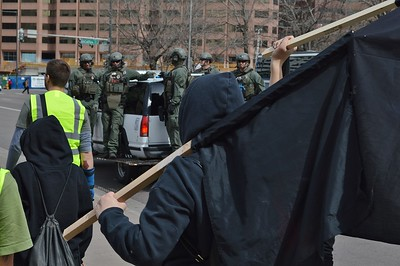 Anti-Trump protesters demonstrate at a march by Trump supporters as Denver police SWAT team looks on.