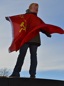 Person wearing Donald Trump mask and flag of the Soviet Union wrapped around them, standing on a wall at Women's March On Denver.