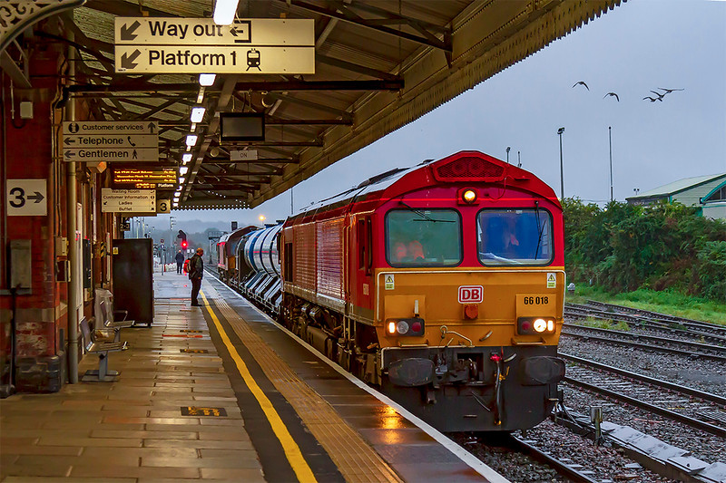 14th Oct 2019:  On a horrible wet Monday evening 66018 on the London end of 3J41 sits in Platform 3 at Westbury as it waits for the green  to deppart for Didcot via the Berks & Hants line. 66069 is on the other end.