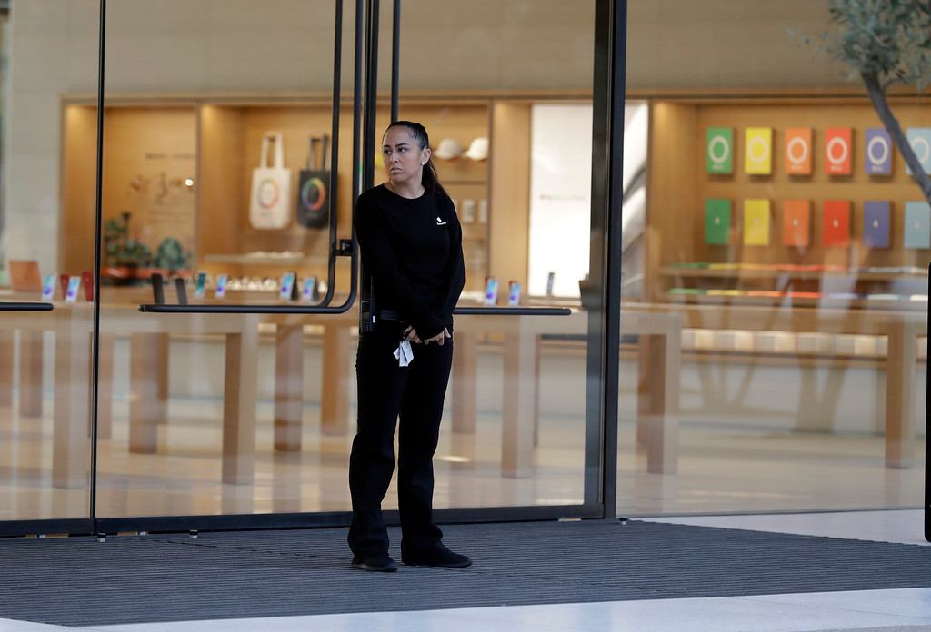. An employee guards the entrance at Apple\'s new visitor center during an announcement of new products Sept. 12, 2017, in Cupertino, Calif. (AP Photo/Marcio Jose Sanchez)