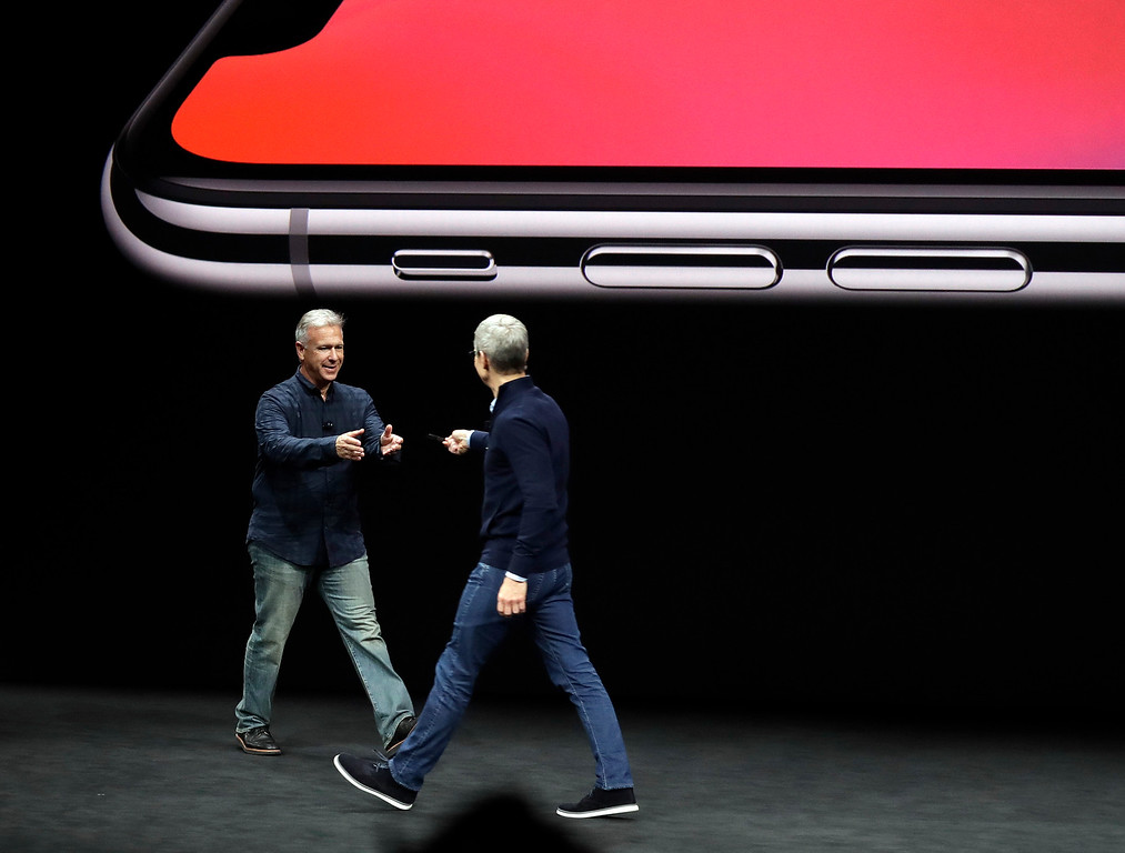 . Phil Schiller, Apple\'s senior vice president of worldwide marketing, left, takes over from CEO Tim Cook as they discuss the features of the new iPhone X at the Steve Jobs Theater on the new Apple campus on Tuesday, Sept. 12, 2017, in Cupertino, Calif. (AP Photo/Marcio Jose Sanchez)