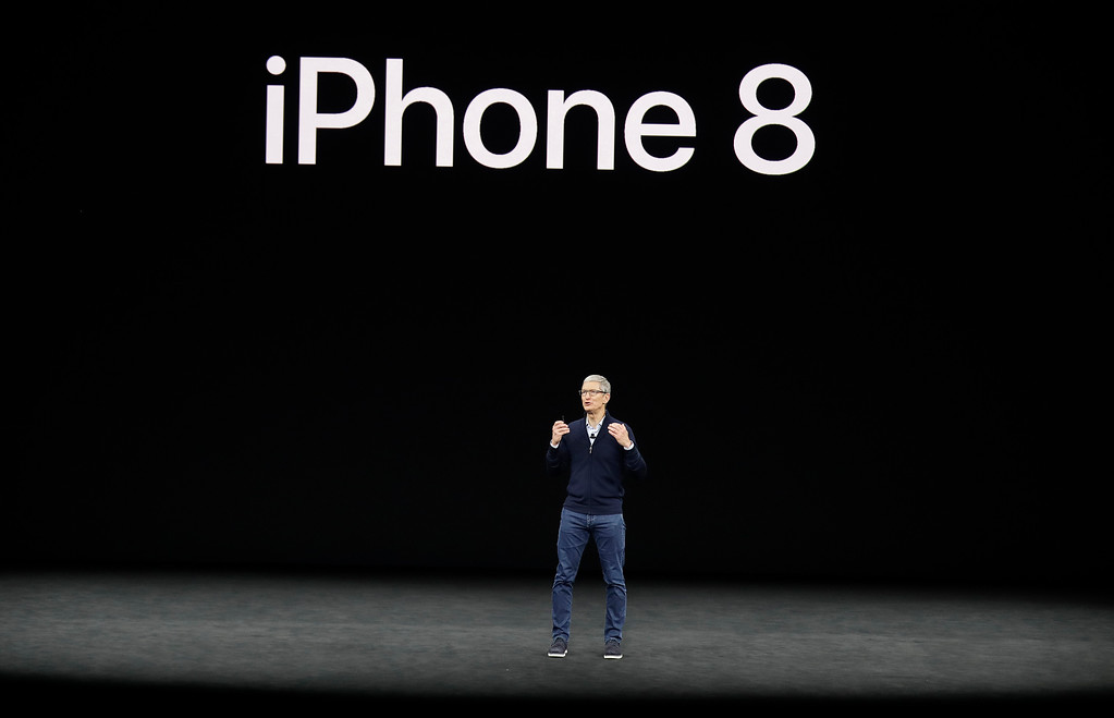 . Apple CEO Tim Cook, shows the new iPhone 8 at the Steve Jobs Theater on the new Apple campus on Tuesday, Sept. 12, 2017, in Cupertino, Calif. (AP Photo/Marcio Jose Sanchez)