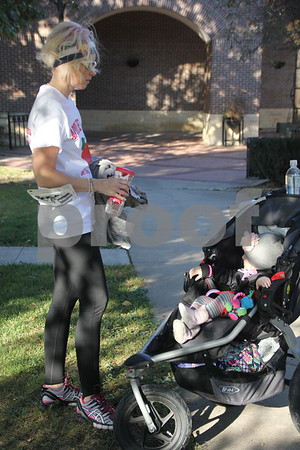 Megan Nickelson (left ) is seen with her little girl ( right and in the stroller, no name given) before she takes part in the annual Applefest 5k/10k run. The event, starting at the Fort Dodge  town square, took place  on Sunday, September 27, 2015.  Megan was one of several who took part in the run.