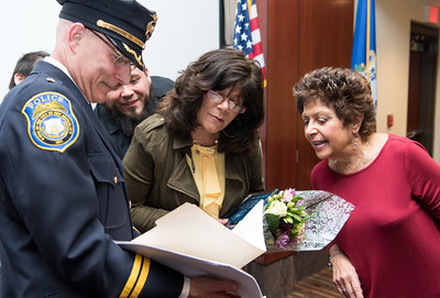 040116   Wesley Bunnell | Staff  New Britain Police honored its own along with two civilians during a presentation at police headquarters Thursday night.  Chief of Police James Wardwell shows Lisa Backus, center, the written citation read during the ceremony while Lisa's sister Elaine Glaski looks on along with Lisa's son Calvin Von Crush over her shoulder.