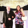 Montserrat College of Art president Stephen Immerman walks the runway with SEARCH graduate during the The Northeast Arc's annual Evening of Changing Lives, Saturday, April 29, at Danversport Yacht Club. [Photo / Nicole Goodhue Boyd]