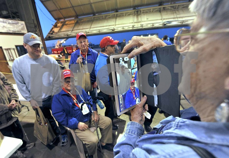 -Messenger photo by Hans Madsen<br /> <br /> Theresa Flickinger, of Fort Dodge, takes a picture of her husband, Korean War Army veteran Elmer Flickinger and their son, Roger Flickinger at the Fort Dodge Regional Airport Saturday morning during the departure for the 14th Brushy Creek Area Honor Flight.
