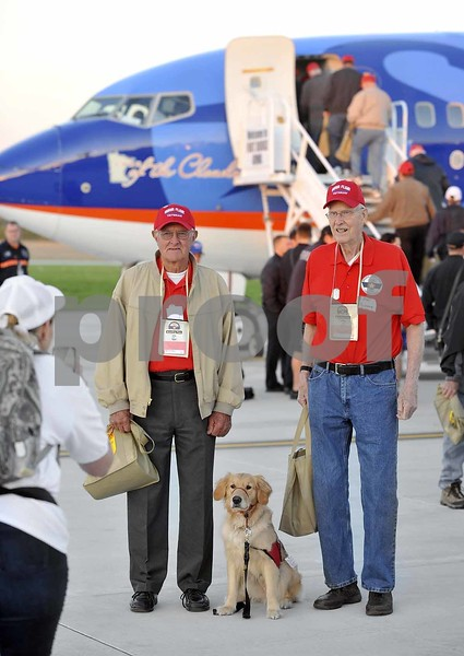 -Messenger photo by Hans Madsen<br /> <br /> Veterans Bernard Kelley, of Terril, at left, along with Bert Nystrom, of Arnold's Park, pose for a picture with Nicole, a service dog from the Puppy Jake Foundation being trained by Kris Dobesh, of Algona, on the tarmac at the Fort Dodge Regional Airport Saturday morning before the departure of the 14th Brushy Creek Area Honor Flight.