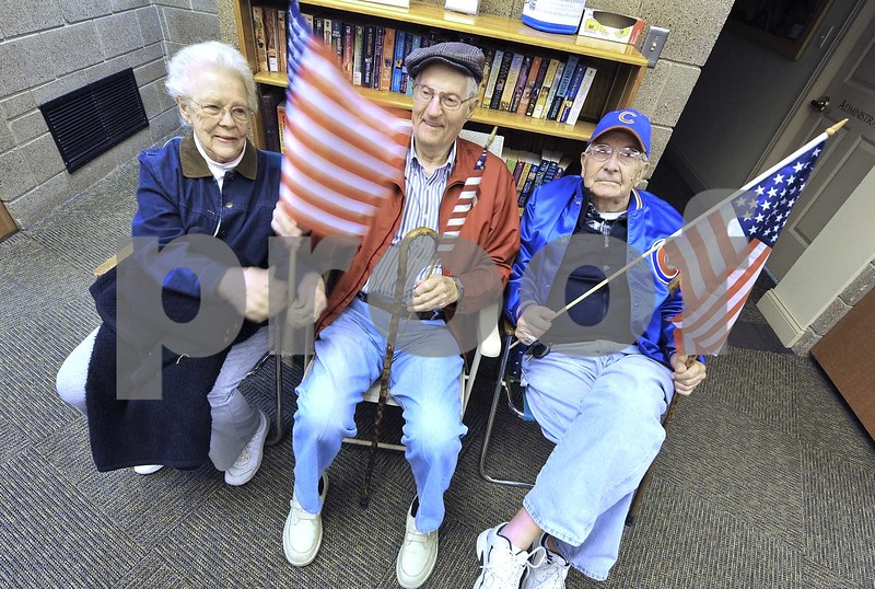 -Messenger photo by Hans Madsen<br /> <br /> Pauline Johnson, at left, along with Ray Norine and Dick Johnson, right, all of Gowrie, get their flags ready Saturday night at the Fort Dodge Regional Airport while waiting for their friend, Air Force veteran Darwin Pelton, of Burnside, to return on the 14th Brushy Creek Area Honor Flight.