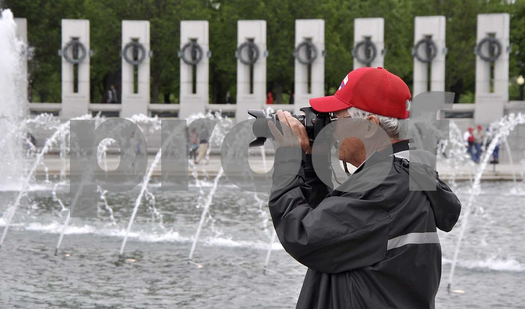 -Messenger photo by Peter Kaspari<br /> <br /> Vietnam War Veteran Gary O'Daniels takes a picture at the World War II Memorial in Washington, D.C. during the Brushy Creek Area Honor Flight. O'Daniels served in the Army.
