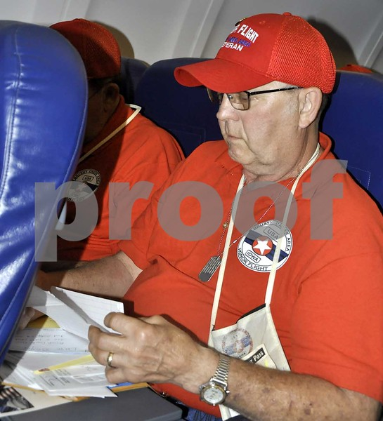 -Messenger photo by Peter Kaspari<br /> <br /> A veteran on the Brushy Creek Area Honor Flight reads his mail from friends and family during the return trip to Fort Dodge.