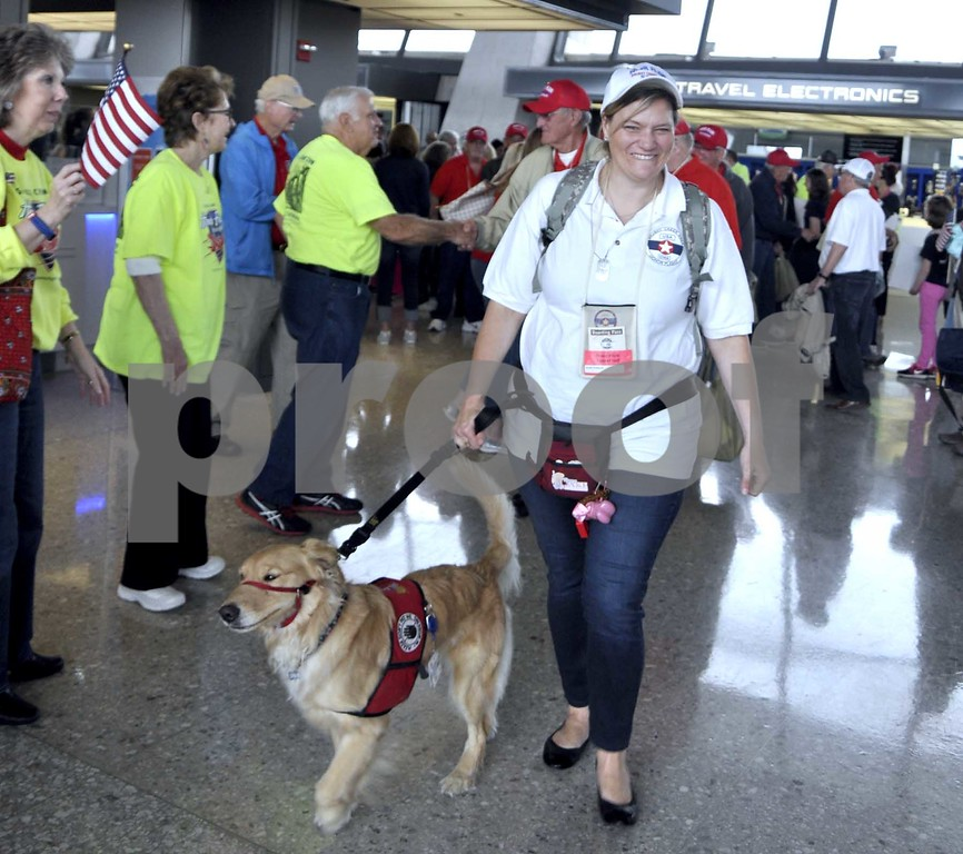 -Messenger photo by Peter Kaspari<br /> <br /> Kris Dobesh, of Algona, a volunteer with the Puppy Jake Foundation, walks with Nicole at Dulles International Airport. Dobesh, who accompanied the veterans on the Brushy Creek Area Honor Flight, is training Nicole to be a service dog for a disabled veteran.