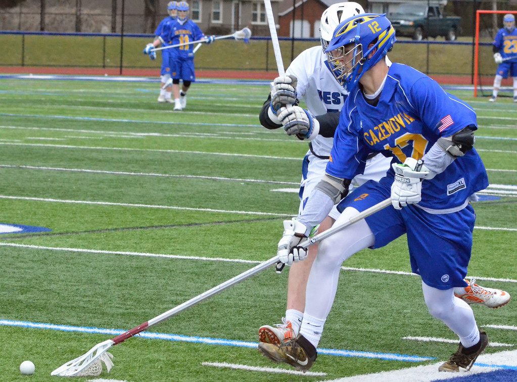 . KYLE MENNIG - ONEIDA DAILY DISPATCH Cazenovia\'s Chris Becker (12) scoops the ball up in front of a Westhill player during their game in Syracuse on Saturday, April 1, 2017.