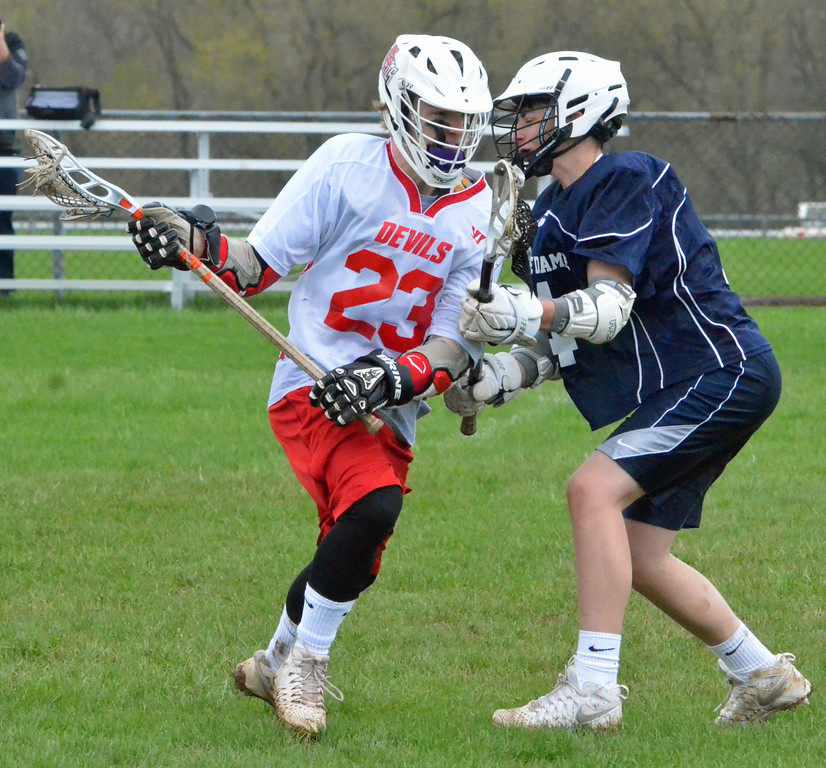 . KYLE MENNIG � ONEIDA DAILY DISPATCH Vernon-Verona-Sherrill\'s Ryan Netzband (21) is checked by Utica Notre Dame\'s Logan Chimento (4) during their game in Verona on Saturday, April 22, 2017.