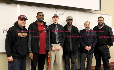 040717 David Glovach | Staff  New Britain's Tristan Wallace, middle, poses with coaches after signing his celebratory letter to play football at Western Connecticut State University. From left to right: Elvin Silva, Tebucky Jones, Tristan Wallace, Justice Hairston, athletic director Len Corto and Carlos Blanco.