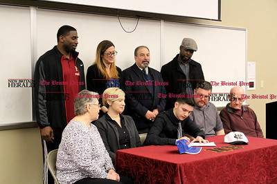 040717 David Glovach | Staff  New Britain's Tristan Wallace, middle, signs is celebratory letter to play football at Western Connecticut State University. Top row from left to right: Tebucky Jones, Kerri-Lynn Major, athletic director Len Corto and Justice Hairston. Bottom row from left to right: grandmother, mother, Tristan Wallace, father and grandfather.