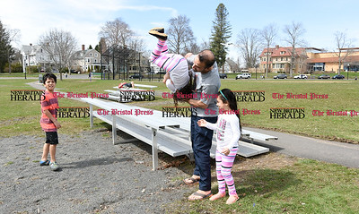 041017  Wesley Bunnell | Staff  Central Park was packed with visitors enjoying a warm spring day on Monday April 10. Ahmed Hamzah catches daughter Safa, age 5, as she jumps into his arms and is flipped upside down as daughter Tuqa, age 6, looks on.