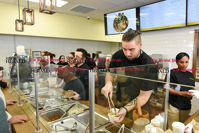 041017  Wesley Bunnell | Staff  Mofongo Restaurant opened its doors to a packed crowd on Monday April 10. Matthew Hayes prepares a meal with owner Vincent Placeres taking an order shown in the middle.
