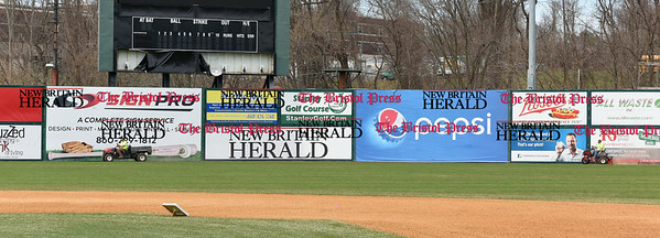 041017  Wesley Bunnell | Staff  Stadium preparation continues at the home of the New Britain Bees on Monday April 10.  Tractors ride across the left field warning track filling in low spots in the clay in front of sponsor signs.