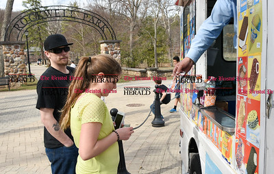 041017  Wesley Bunnell | Staff  Rockwell Park was packed with visitors eager to take advantage of the warm spring weather on Monday April 10. Piper Kamens, age 11, receives her Choco Taco ice cream sandwich from the ice cream truck.