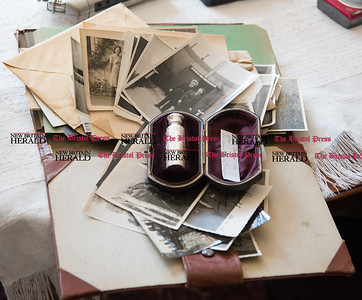 030617  Wesley Bunnell | Staff  Farmington resident Ola Ferla served as an Army Nurse during WWII in Scotland and England. A perfume bottle given by a friend in England sits atop photos from the war.