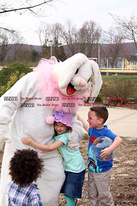 Leah Murphy and Zachary Harrison greet the Easter Bunny at Stocks Playground with their licensed childcare providers.