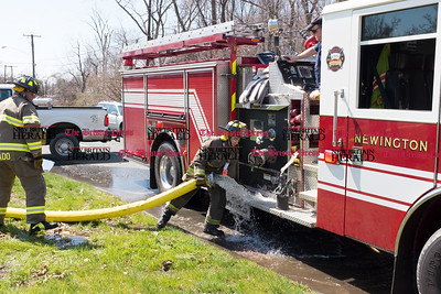 041317  Wesley Bunnell | Staff  At the scene of a fire at Tilcon in Newington a Newington Firefighter struggles to lift the 5 inch diameter hose from a hydrant to the side of Engine 2 on Thursday afternoon. Due to the long length of approximately 2,200 feet of hose needed Engine pumped water in relay with another engine up to the scene.