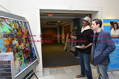 041217  Wesley Bunnell | Staff  The New Britain Artists' Co-op held a reception at City Hall on Wednesday evening featuring work by co-op members. Co-op artists Walter Cloud, left stands with Kendall Soliwoda while discussing Soliwoda's work.