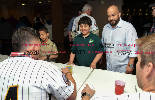 041817 Wesley Bunnell | Staff The New Britain elks Lodge 957 held their 35th Annual Welcome Baseball Dinner featuring The New Britain Bees on Tuesday evening. Craig Maddox (24) signs an autograph for Xavier Robles, age 9, and his father Eliasin Robles.