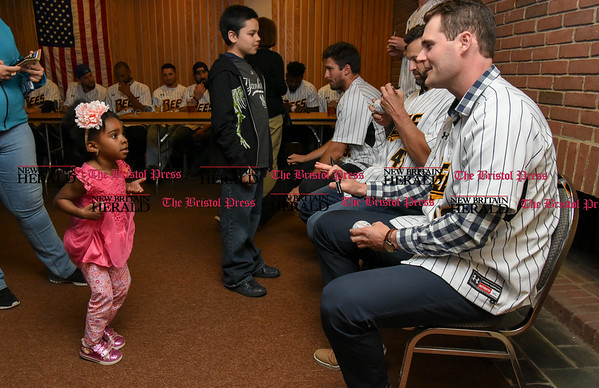 041817 Wesley Bunnell | Staff The New Britain elks Lodge 957 held their 35th Annual Welcome Baseball Dinner featuring The New Britain Bees on Tuesday evening. Nariah Pierre, age 4, looks up at pitcher Brian Dupra (30) as he prepares to autograph her baseball.