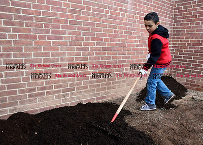4/22/2017 Mike Orazzi | Staff Julian Suarez spreads mulch during the 16th annual Comcast Cares Day at the Smith Elementary School in New Britain Saturday.