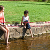 042817  Wesley Bunnell | Staff<br /> <br /> Zuleika Casiano sits along a stream at A.W. Stanley Park as she waits for son Justin Serrano, age 4, to stick his feet in to cool down on a warm Friday afternoon.