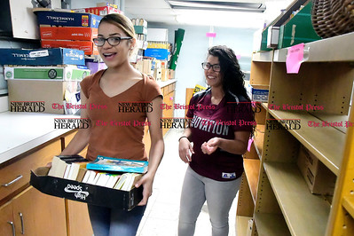 4/29/2017 Mike Orazzi | Staff Stephanie Ortiz and Lucielle Rodriguez while sorting Polish books at the New Britain Public Library Saturday.