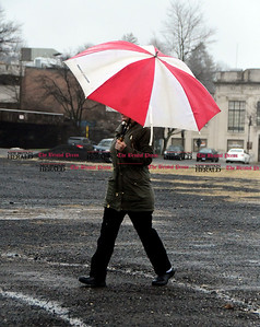 4/4/2017 Mike Orazzi | Staff A woman shields herself from rain while walking in Centre Square in downtown Bristol Tuesday.