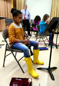 4/6/2017 Mike Orazzi | Staff Ken Bagley, citywide coordinator for music director, as South Side School 4th grade students Lily Hinton Alison Sarmiento and Gwen Tanner Thursday.