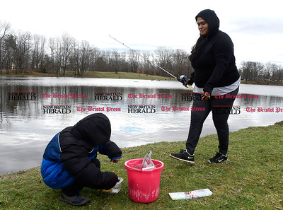 4/8/2017 Mike Orazzi | Staff Andre Arroyo looks for worm while fishing with his mother Marisol during the New Britain Parks and Recreation Department's annual Fishing Derby held at the pond in Stanley Quarter Park Saturday morning.
