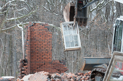 04/02/18  Wesley Bunnell | Staff  Demolition of a house adjacent to Kensington Congregational Church started on Monday which is the first step in an expansion to the church property.  The excavator plucks the last remaining window from a corner of the garage.