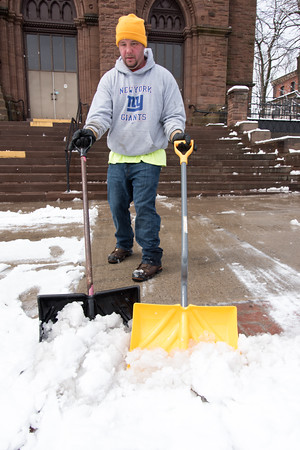 04/02/18 Wesley Bunnell | Staff Chris Avallone of Chris' Snow Removal uses two shovels to push the snow and slush mixture from the sidewalks in front of St. Mary Church on Main St. in New Britain on Monday afternoon.