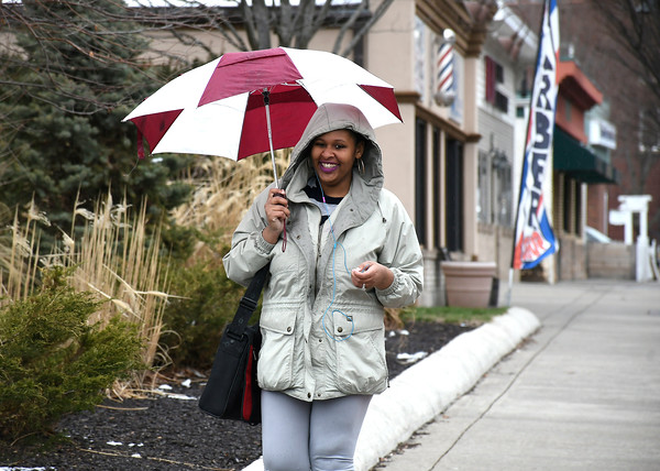 4/3/2018 Mike Orazzi | Staff Tinaza Banks shields herself from rain while walking on North Main Street in Bristol Tuesday afternoon.