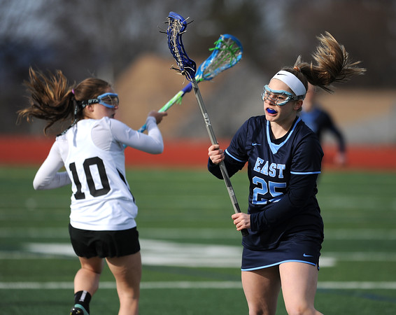 4/11/2018 Mike Orazzi | Staff Bristol Co-op lacrosse's Lily Hansen (10) and East Catholic's Lily Ryan (25) at Bristol Central Wednesday.
